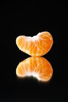 Вид спереди маленький кусочек мандарина на черной стене напиток дерево цитрусовый сок темнота апельсин грейпфрут