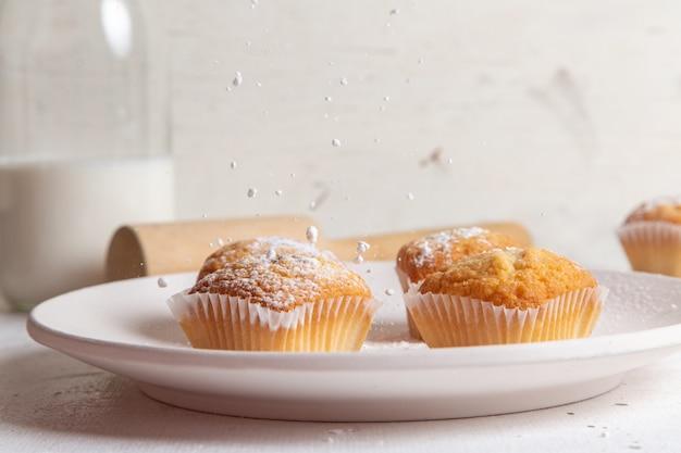 Vista frontale di piccoli gustosi dolci con zucchero in polvere sulla superficie bianca