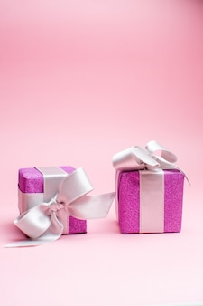 Front view little xmas presents on a pink christmas color gift photo new year holiday
