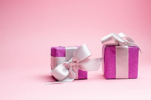 Vista frontale piccoli regali di natale su foto regalo di colore rosa di natale vacanze di capodanno