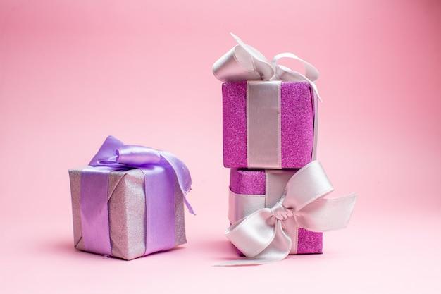 Vista frontale piccoli regali di natale sulla foto rosa del regalo di natale colore delle vacanze di capodanno