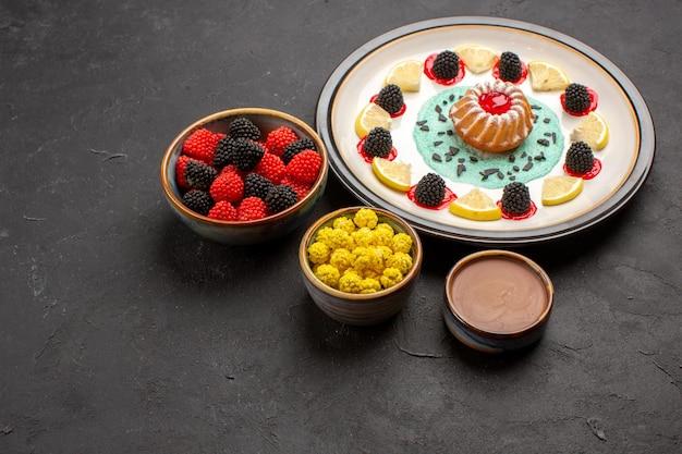 Вид спереди маленький вкусный торт с ломтиками лимона и конфетами на темном фоне фруктовое цитрусовое печенье, печенье, сладкое