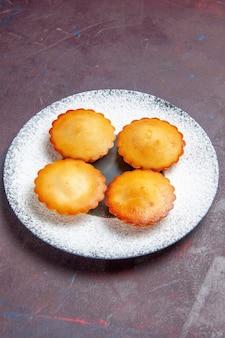 어두운 배경 달콤한 파이 비스킷 쿠키 차 케이크에 접시 안에 있는 작은 맛있는 케이크 전면 보기
