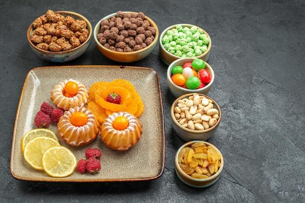 Vista frontale piccole deliziose torte con caramelle e noci su spazio grigio