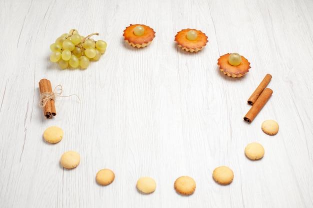 正面図白い机の上のブドウとクッキーと小さなおいしいケーキフルーツケーキビスケット甘いデザートティー