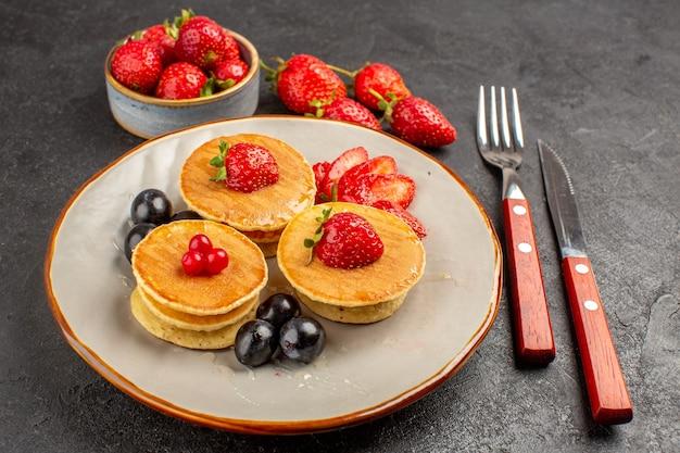 Vista frontale piccole frittelle gustose con frutta sulla torta di frutta torta superficie scura