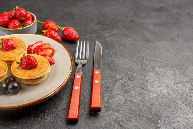 Вид спереди маленькие вкусные блины с фруктами на темной поверхности пирога фруктовый торт