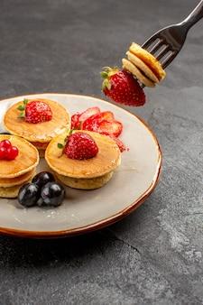 Вид спереди маленькие вкусные блины с фруктами на серой поверхности пирога с фруктами