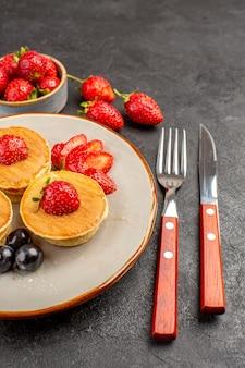어두운 표면 파이 과일 케이크에 과일과 함께 전면보기 작은 맛있는 팬케이크