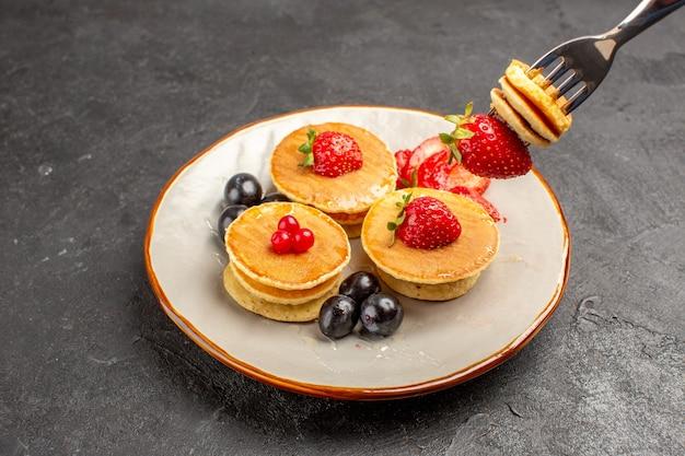 正面図灰色の表面のパイケーキフルーツにフルーツと小さなおいしいパンケーキ