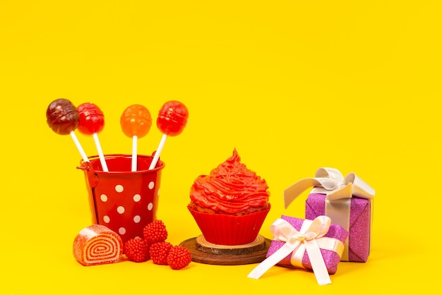 A front view lollipops and cake with marmalade and purple gift boxes on yellow, color sugar biscuit