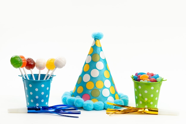 A front view lollipops and candies colorful inside baskets along with birthday cap on white, candy sweet sugar color