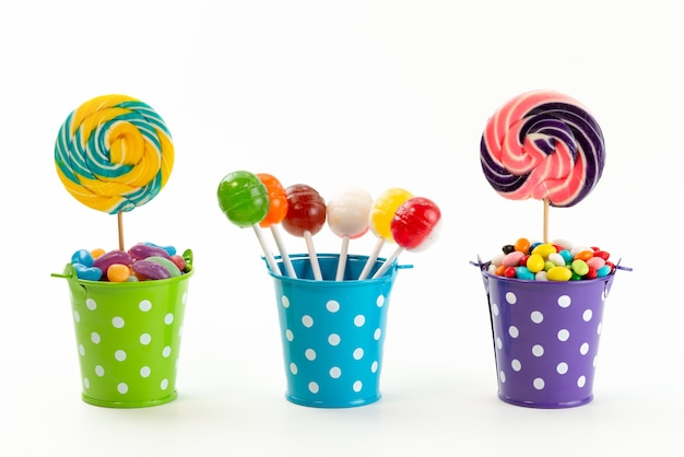 A front view lollipops and candies inside little baskets on white, sugar sweet confiture color