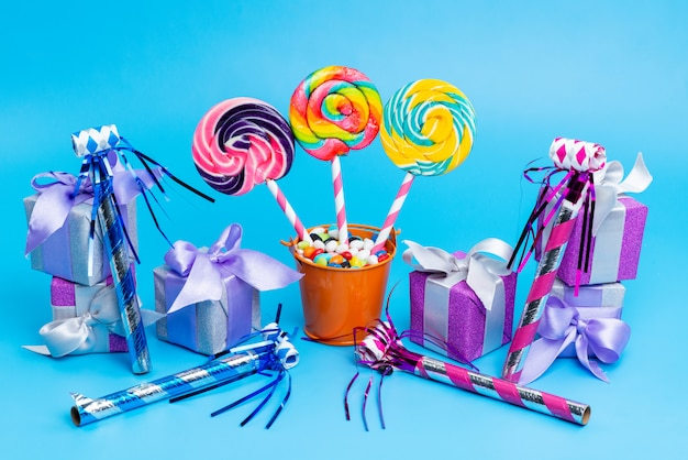 A front view lollipops and candies with little gift boxes birthday whistles on blue