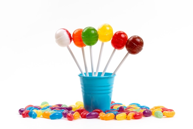 A front view lollipops inside bucket along with multicolored marmalades on white, sugar sweet rainbow