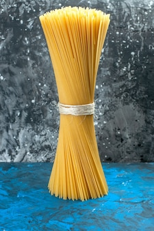 Vista frontale pasta italiana lunga prodotto crudo legato al pasto a luce blu molti pasta alimentare foto a colori