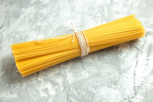 正面の長いイタリアン パスタ生は、明るい写真の食品の色の多くの生地に結ばれています。