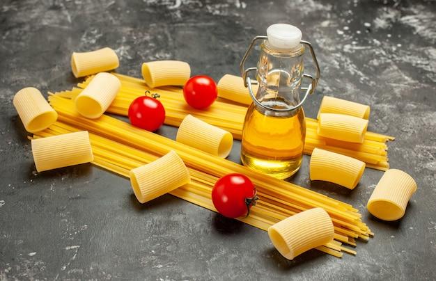 正面図の長いイタリアン パスタと明るい灰色の食品の色の生地の料理の食事に赤いトマトを添えた