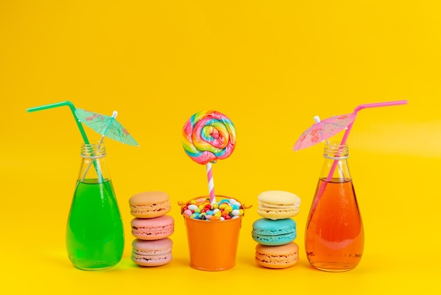 Una vista frontale macarons e cocktail colorati con caramelle e lecca-lecca su giallo, arcobaleno di biscotti torta di colore
