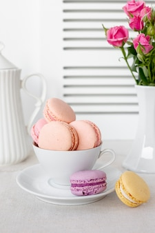 Front view of macarons in cup with roses