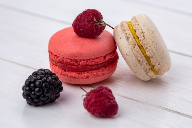 Front view of macarons with blackberries and raspberries on a white surface
