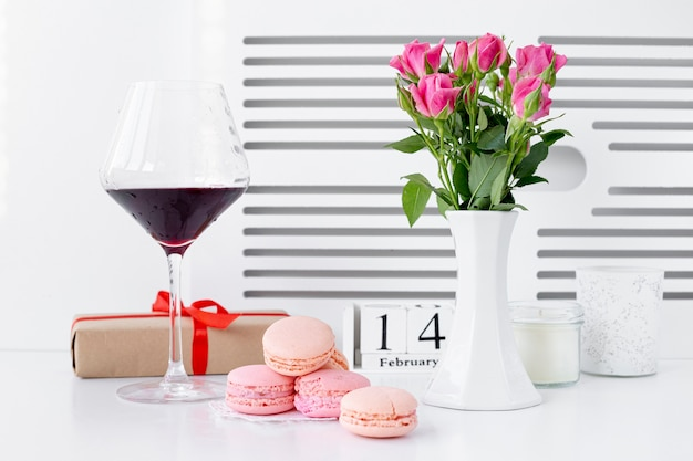 Front view of macarons with wine glass and vase of roses