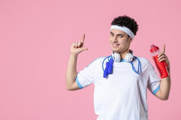 Спортсмен-мужчина в спортивной одежде с бутылкой воды, вид спереди