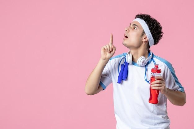 水のボトルとスポーツ服を着た男性アスリートの正面図