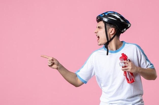 Спортсмен-мужчина в спортивной одежде, шлем и бутылка воды, вид спереди