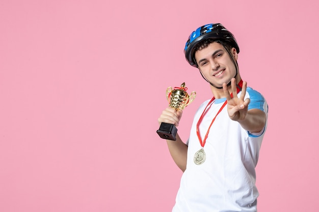 Front view male athlete in sport clothes holding golden cup with helmet