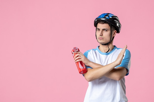 Front view male athlete in sport clothes with helmet and bottle of water