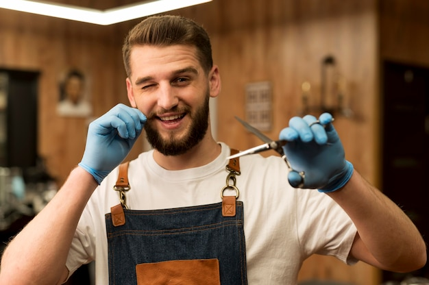 Front view of male barber holding scissors in the barbershop