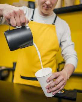 Front view of male barista pouring milk in cup