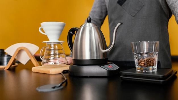 Front view of male barista preparing coffee with kettle and filter