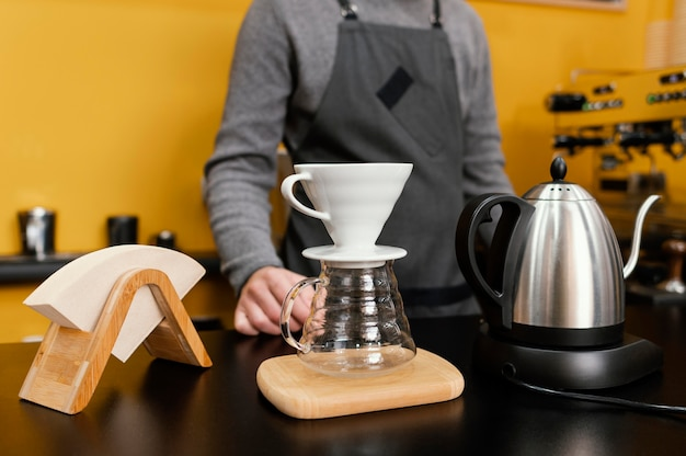 Front view of male barista with coffee filter and kettle on the counter