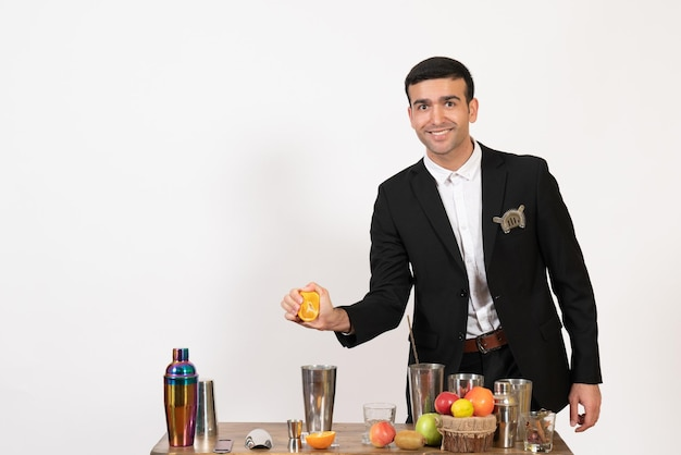 Front view male bartender in classic suit making drink squeezing orange on a white wall night club male bar dance drink