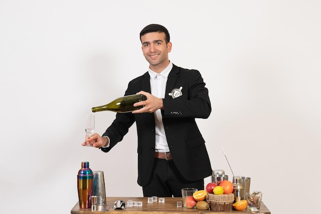 Front view male bartender in classic suit making drink on white desk night club male bar drink alcohol
