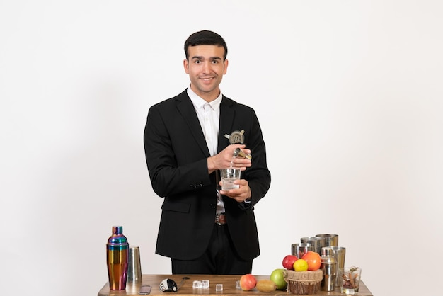 Front view male bartender in classic suit making drink on white wall night club male bar dance drink