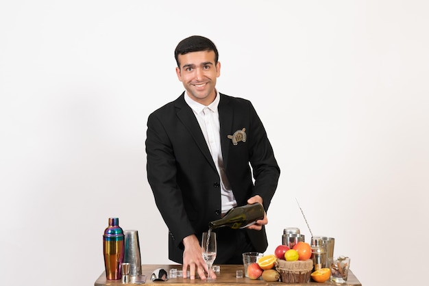 Front view male bartender in classic suit making drink on white wall night club male bar drink alcohol