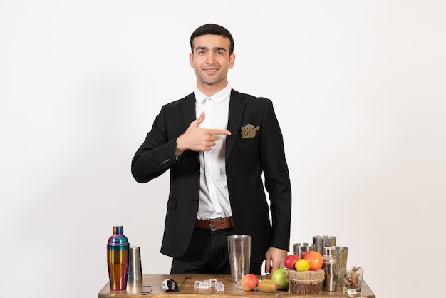 Front view male bartender in classic suit making drink on the white wall night drink club male bar dance