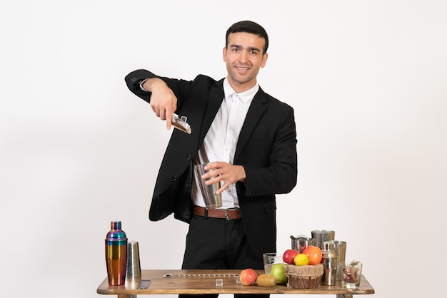 Front view male bartender in classic suit making drink on white wall night drink club male bar dance