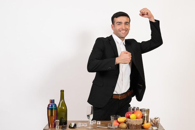 Front view male bartender in classic suit standing and posing on light white wall night club male bar drink alcohol