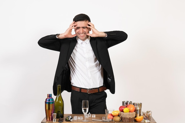 Front view male bartender in classic suit standing and posing on white desk night club male bar drink alcohol