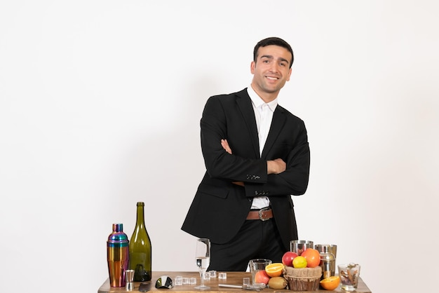 Front view male bartender in classic suit standing and posing on white wall night club male bar drink alcohol