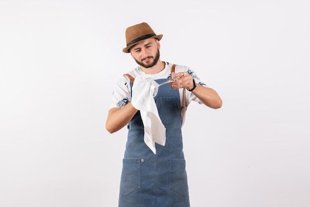 Вид спереди мужчина-бармен, чистящий стекло на белой стене, ночная работа, клуб, алкогольные напитки, цветная полоса
