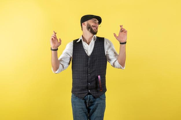 Vista frontale barista maschio incrociando le dita sulla parete gialla bere club maschio alcol lavoro night bar