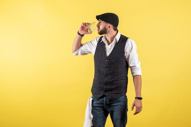 Vista frontale barista maschio che beve dal bicchiere sulla parete gialla bere alcol lavoro club bar notte male