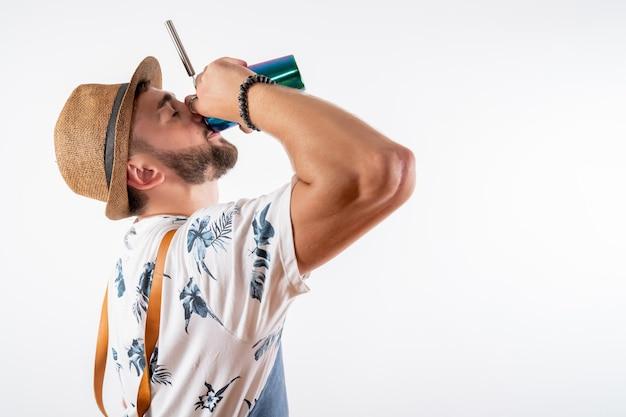 Barista maschio vista frontale che beve succo dallo shaker su un muro bianco night bar alcol club drink job
