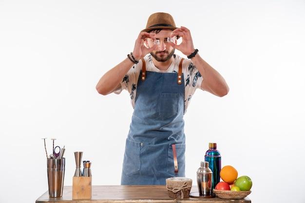 Barista maschio vista frontale davanti alla scrivania con shaker e frutta che tengono cubetti di ghiaccio sul muro bianco lavoro bar alcol club servizio di bevande notturne