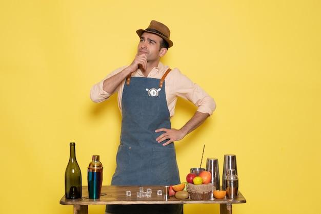 Barista maschio vista frontale davanti al tavolo con bevande e shaker pensando al muro giallo notte alcol maschio club bar drink